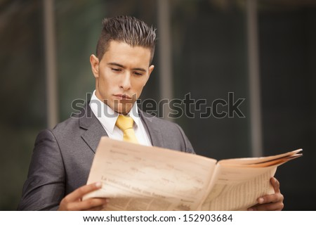 Businessman reading his newspaper next to his office building - stock photo