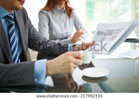 Businessman reading newspaper and having coffee in office - stock photo