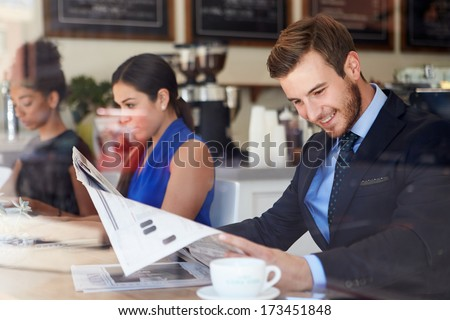 Businessman Reading Newspaper In Coffee Shop - stock photo