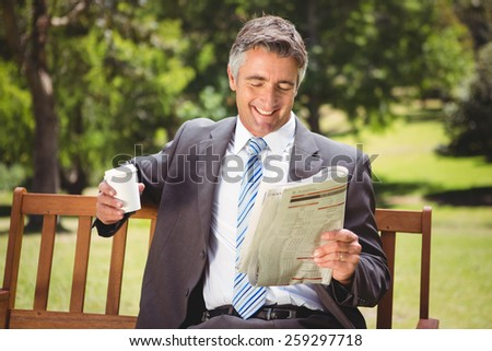 Businessman reading newspaper in the park on a sunny day - stock photo