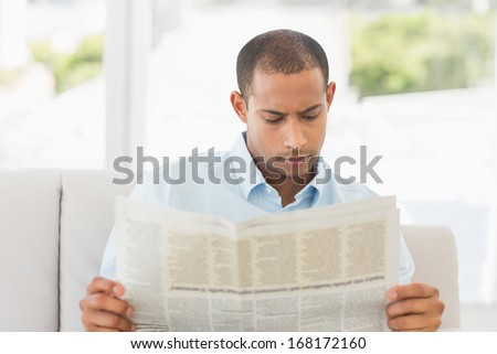 Businessman reading newspaper on the couch in the office