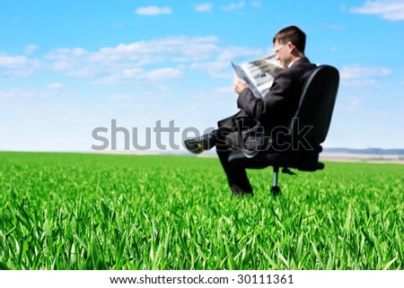 Businessman reading newspaper sitting on chair in green field