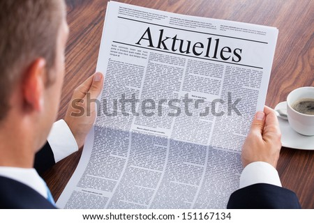 Businessman Reading Newspaper With The Headline Current News - stock photo