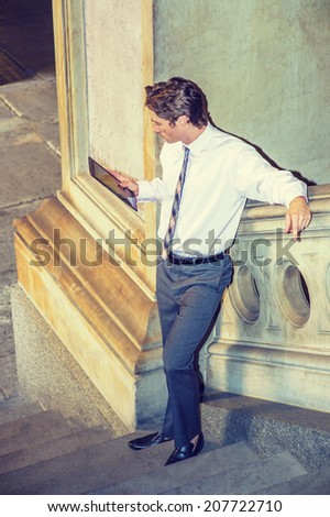 Businessman Reading Outside. Dressing in a white shirt, patterned neck tie, gray pants, leather shoes, a young businessman is standing on stairs by a railing, looking down, reading on tablet computer. - stock photo