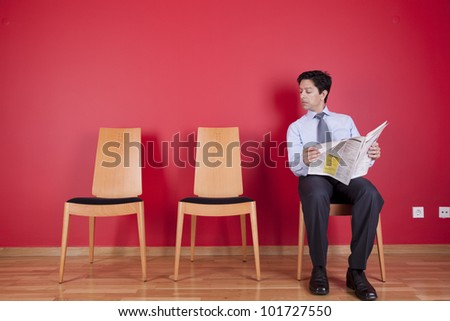 businessman reading the newspaper siting on a chair - stock photo