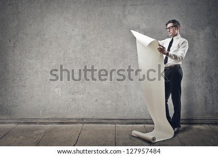 businessman reads the paper roll on gray background - stock photo
