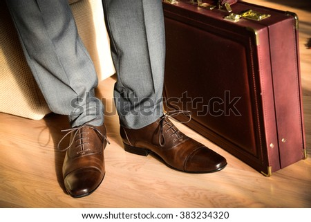 Businessman ready to put on the shoes and leather suitcase next to his feet. - stock photo