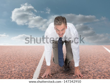 Businessman ready to run and looking at camera - stock photo