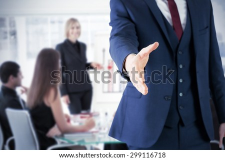 Businessman ready to shake hand against businesswoman reporting to sales in a seminar - stock photo