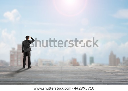 Businessman rear view gazing at city on old wooden floor, sunny day