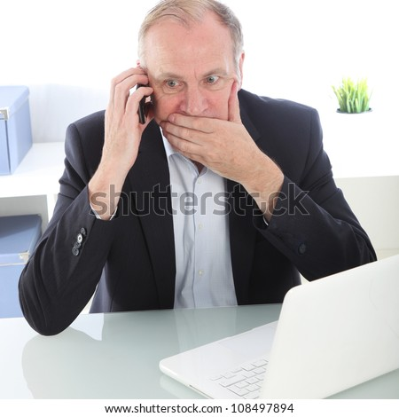 Businessman receiving bad news Businessman seated at his desk covering his mouth with his hand in shock as he receives bad news over his mobile phone