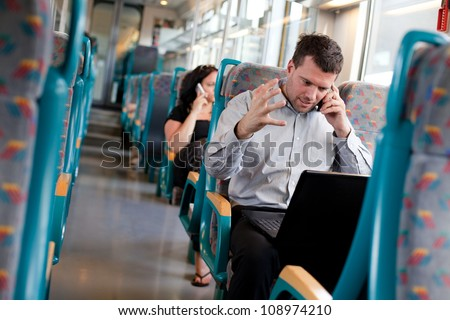 Businessman receiving bad news on a train - stock photo
