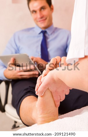 Businessman receiving foot massage from therapist - stock photo