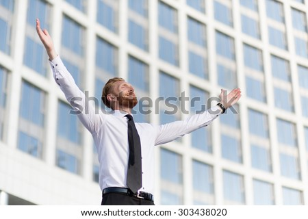 Businessman rejoicing for his success. Red-haired man in white shirt and tie looking at the sky and happy celebrating his victory. - stock photo