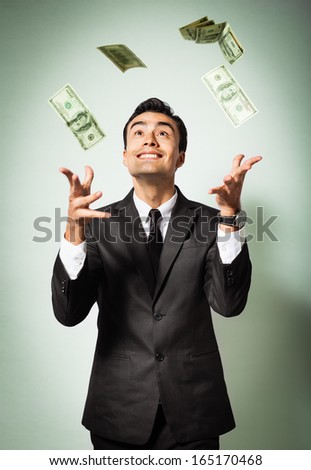Businessman rejoicing for his success with hundred dollar banknotes flying in the air