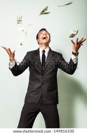 Businessman rejoicing for his success with hundred-dollar banknotes flying in the air. Happy businessman in a rain of money.
