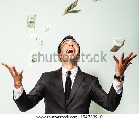 Businessman rejoicing for his success with hundred dollar bills. Money rain. - stock photo