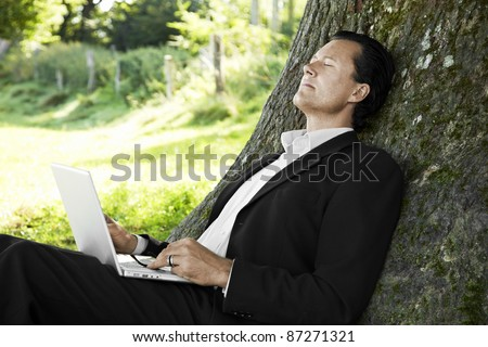 Businessman relaxing against a tree with his laptop - stock photo