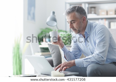 Businessman relaxing at home in the living room, he is sitting on the sofa, having a coffee and working with a laptop
