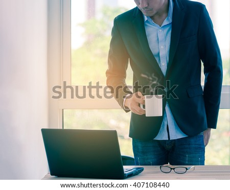 Businessman relaxing by coffee cup while working. - stock photo