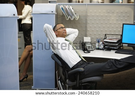 Businessman Relaxing in Cubicle - stock photo
