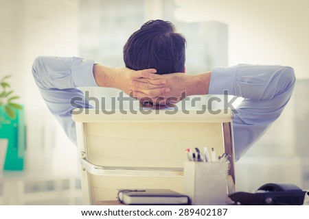 Businessman relaxing in his chair in the office