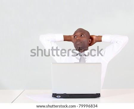 Businessman relaxing in office in front of laptop computer - stock photo