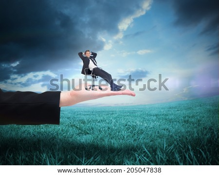 Businessman relaxing in swivel chair against blue sky over green field