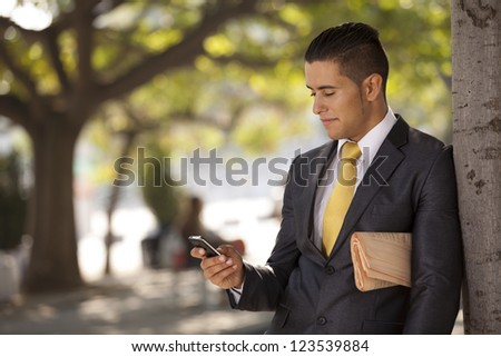 Businessman relaxing next to a tree at the city park, sending short messages over his cellphone