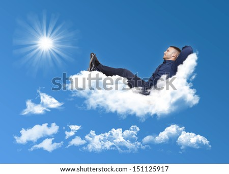businessman relaxing on a cloud in a blue sky with sun