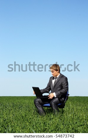 Businessman relaxing on green grassland under blue sky