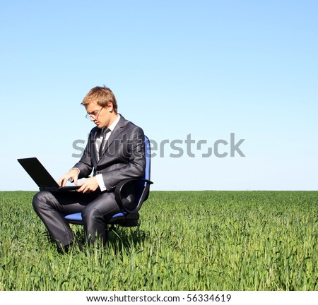 Businessman relaxing on green grassland.Under blue sky - stock photo