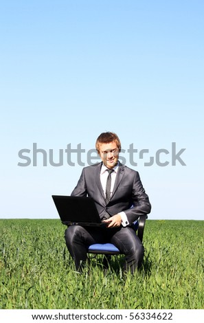 Businessman relaxing on green grassland under blue sky - stock photo