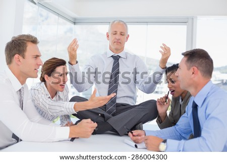Businessman relaxing on the desk with upset colleagues around in the office - stock photo
