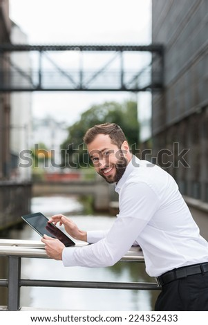 Businessman relaxing outdoors with his tablet leaning on the parapet of a small urban bridge turning to smile at the camera