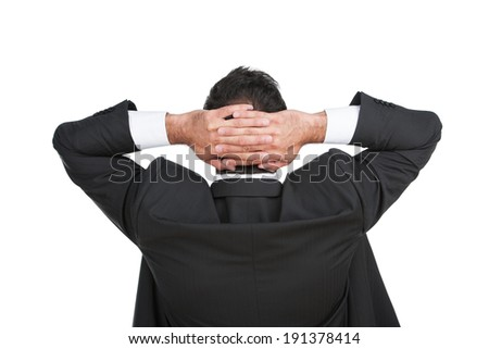 Businessman Relaxing. Rear view of businessman relaxing with his hands clasped behind his head