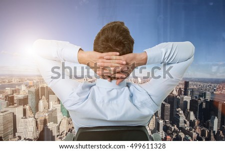 Businessman relaxing while looking at the city from his office window