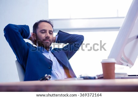 Businessman relaxing with hands behind head while sitting in bright office