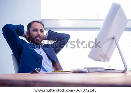 Businessman relaxing with hands behind head while sitting in creative office