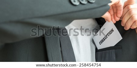 Businessman removing or placing a white card with word Corruption in the inner pocket of his suit jacket, close up view of the card. - stock photo