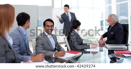 Businessman reporting sales figures to his team in the office - stock photo