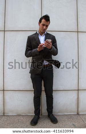 Businessman resting from work and while sending messages and talking with his smart phone.  - stock photo