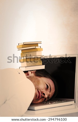 Businessman resting head on laptop keyboard against grey room - stock photo