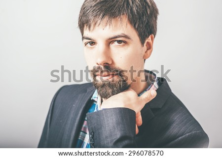 businessman resting his chin in his fist with a beard - stock photo
