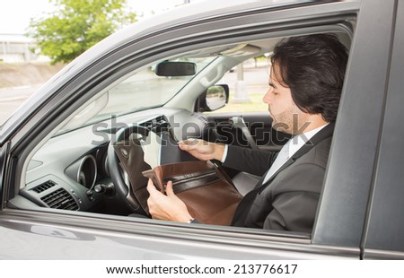 Businessman reviewing documents in the car