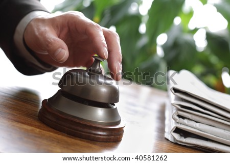 Businessman ringing a hotel reception service bell to attract attention - stock photo