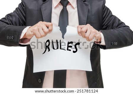 Businessman ripping up the RULES sign on white background - stock photo