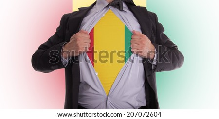 Businessman rips open his shirt to show his Guinea flag t-shirt