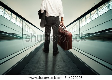 Businessman rise with an escalator with baggage