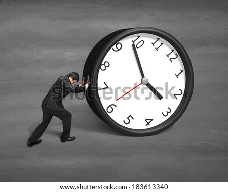 Businessman rolling clock on concrete ground